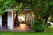 Sonnenlicht auf überdachte Veranda eines kanadischen Landhauses mit Rasenfläche und Laubbaum