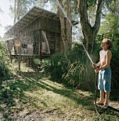 A boy spraying water near a forest hut