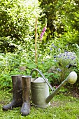 A watering can and a pair of wellington boots in garden