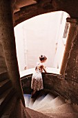 A woman leaning on a staircase balustrade and looking out