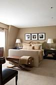 Elegantes Schlafzimmer mit beigefarbenen Polsterbett, Ton in Ton mit Wandfarbe und Teppichboden