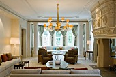 Sofa combination in grand, British manor house with lit chandelier and table lamps