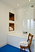 Minimalist, white, designer bathroom with towels in niches, glass shower screen, blue floor and rustic wooden chair