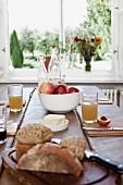 Gedeckter Holztisch mit Vollkornbrot, Brötchen, Butter, Obst und Apfelsaft