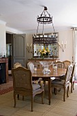 Country-house dining room with upholstered period chairs and wreath-shaped candle chandelier