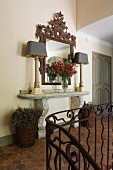 Elegant, stone console table, ornate mirror and table lamps in terracotta-tiles hallway in historical, French country house