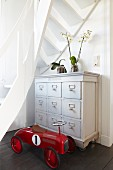 Red, vintage bobby car in front of white-painted chest of drawers under white, winding wooden staircase
