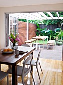 Modern dining area in front of open folding doors leading to terrace