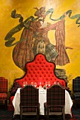 Mural of highland Scot behind set table and bench with tall, curved backrest in the Dorchester Hotel, London