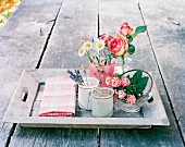 Various summer flowers in different vessels on tray on garden table