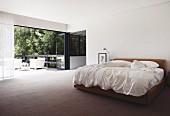 Minimalist bedroom with double bed and open folding terrace door with view of garden