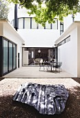 Metal sculpture on ground in front of patio with outdoor furniture outside contemporary house