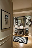 Framed portrait of woman on wall of hallway with view of Fornasetti chairs and black and white houndstooth rug