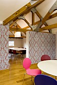 Colourful, retro shell chairs around white table; partition covered in patterned wallpaper and conference table and chairs in background