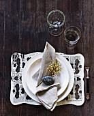 Name written on pebble on linen napkin and newspaper place mat with pattern of holes on rustic wooden table