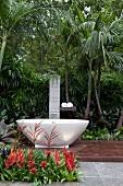 Free-standing, oval designer bathtub on wooden platform in front of tropical planting