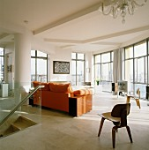 Wooden designer chair and sofa with orange upholstery in living room of penthouse apartment with floor-to-ceiling windows