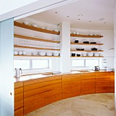 Cherry wood base cabinets and shelves on curved wall in penthouse apartment
