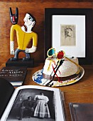 Sunglasses on painted hat, books and painted wooden figurine on table