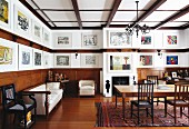 Living room with dining area, antique benches, half-height wooden cladding and gallery of artworks