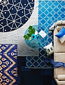 Rugs in shades of blue with various patterns in living room with glass table and sofa