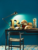 Jointed table lamp, decorative letter and antiquarian books on desk against blue wall