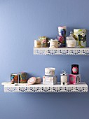 Various scented candles on metal shelves with punched trim