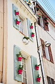 Pale house facade with red plant pots hung on window shutters