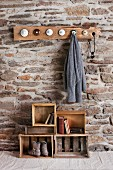 Rustic DIY cloakroom in room with stone wall; coat pegs made from old china lids and old wooden crates on floor as storage