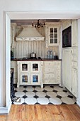 Open doorway with view into shabby-chic kitchen area with white cupboards, some with lattice doors, and white-tiled floor with black accent tiles