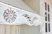 Detail of wooden extractor hood painted white and carved with rosettes