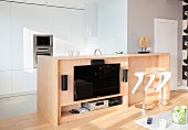 Flatscreen TV mounted on wooden counter and designer bar stools with white seats in open-plan kitchen area