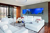 Modern sofa set with white leather covers and coffee table in lounge area; large aquarium incorporated in grey-tiled wall