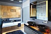 Modernes Bad, Waschtisch mit zwei schwarzen Aufbaubecken, oberhalb Spiegel mit integrierter Beleuchtung, im Hintergrund Badewannenfront und Wand mit Fliesen in Messing-Optik