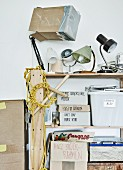 Artistic jumble of vintage lamps and labelled cardboard boxes on shelves