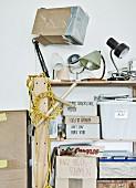 Künstlerisches Chaos mit Vintage Leuchten und beschrifteten Pappschachteln auf einem Regal