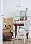 Eclectic dining area with retro furnishings and vintage dresser in youthful kitchen-dining room