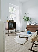 Eclectic, youthful interior with Chippendale-style TV cabinet on castors, sheepskin rugs and ride-on toy car on chest of drawers