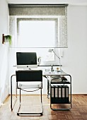 Cantilever chair with leather seat and classic desk in front of half-closed, translucent roller blind