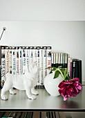 Hundefigur aus weißem Porzellan neben Vase mit fuchsiafarbener Pfingstrose vor Büchersammlung auf Ablage aus Edelstahl