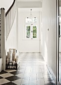 Traditional entrance with painted, chequered wooden floor and staircase to one side