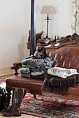 Pulloverstapel und Decken auf antiker Sitzbank mit braunem Lederbezug und geschnitztem Holzgestell in ländlich, traditionellem Schlafzimmer