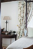 Four-poster bed next to antique, semicircular side table made from dark wood