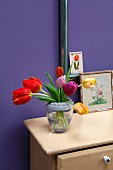 Tulips in various colours in glass vase with circular, hand-crafted concrete rim on cabinet against purple wall