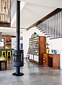 Freistehender Kaminofen auf Estrichboden, seitlich halbhoher Schrank und Vintage Regalschrank an Treppenhauswand in offenem Wohnraum