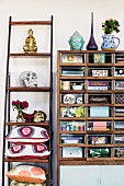 Vintage shelving unit next to Buddha figurine and skull ornament on ladder-style shelving