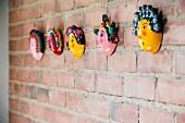 Row of small, painted masks on brick wall