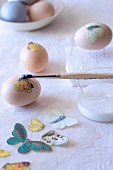 Decorating eggs - applying decoupage butterfly motif using glue