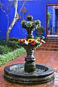 Pool with ornamental, tiered fountain decorated with flowers in courtyard with terracotta tiles and blue wall in background