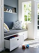 Sitzbank mit grauer Sitzauflage & Zierkissen in Nische am Fenster darunter Schubladen als Stauraum für Spielsachen
